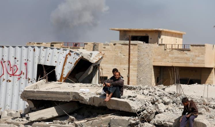 مدنيون ينتظرون المساعدات الغذائية بينما تتصاعد أعمدة الدخان من مناطق القتال غربي الموصل (رويترز)