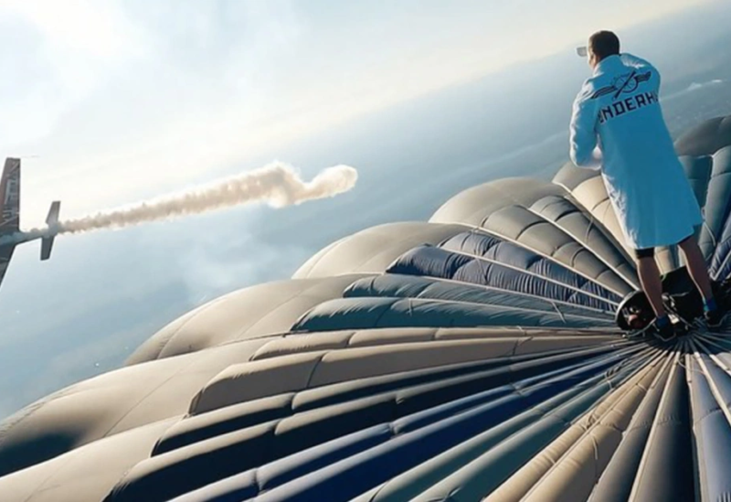 شاب يقف أعلى بالون ضخم ممسكا بفنجان القهوة ويلوح لطائرة